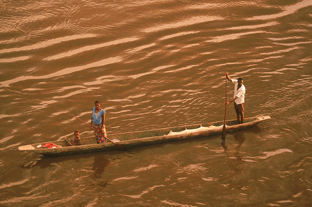 A family in their dugout canoe or pirogue paddles across the brown water of the Congo River.
