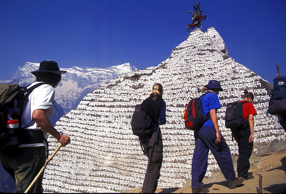 Young trekkers from New Zealand pass a stupa in Namche Bazzar while trekking in the Khumbu region (on the way to Everest), Nepal