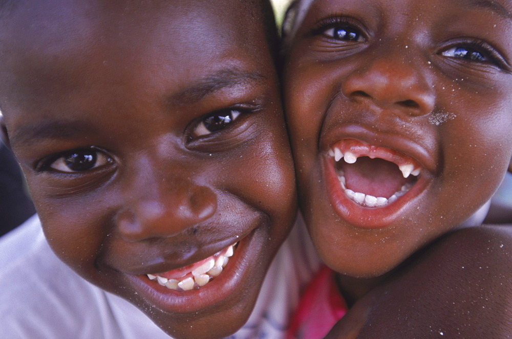 A brother and sister share a laugh and a hug at their home on Cat Island in the Bahamas.
