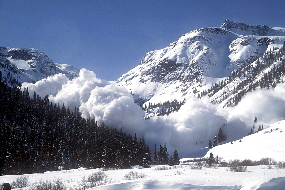 At an avalanche area near Silverton, Colorado in the San Juan Mountains a helicopter has dropped explosives to set off a slide while the road is closed. This stretch of highway receives more avalanches than any other in North America.