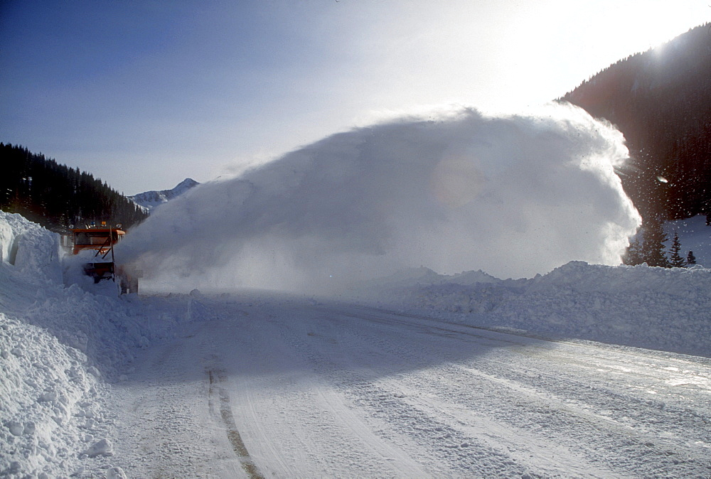 At an avalanche area near Silverton, Colorado in the San Juan Mountains a plow clears snow from the road after an avalanche was safely set off while the road is closed. This stretch of highway receives more avalanches than any other in North America.