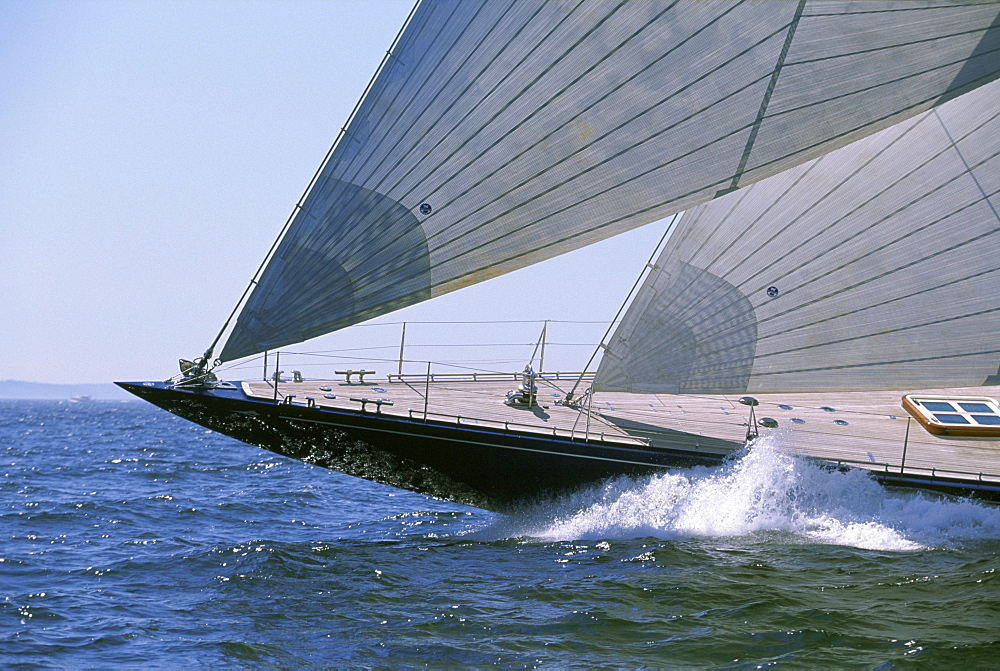 A traditional racing yacht, a 130 foot J-Class Sloop, sails ahead.