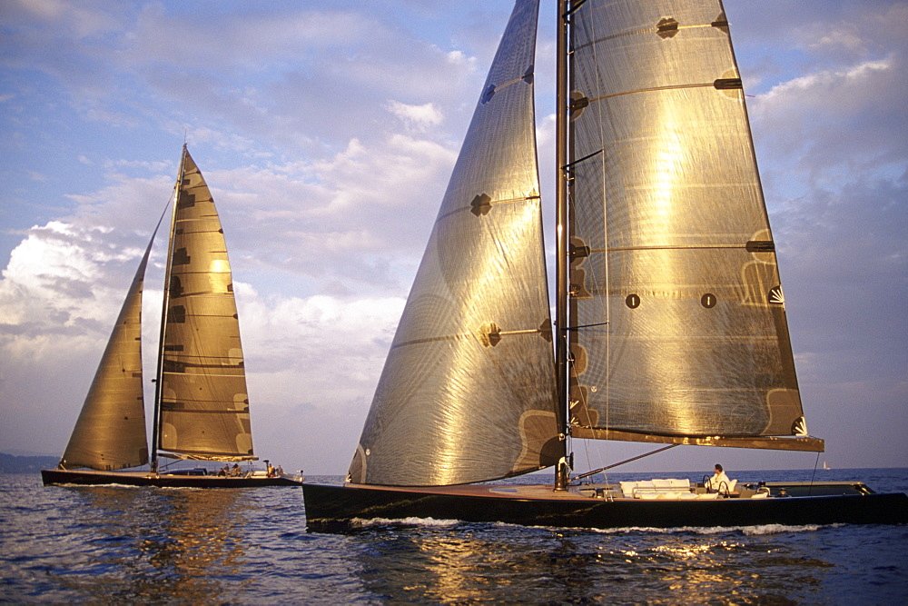 Two modern racing yachts sail in light air at sunset at Les Voiles de St.Tropez, France. The sails glisten like woven silver.