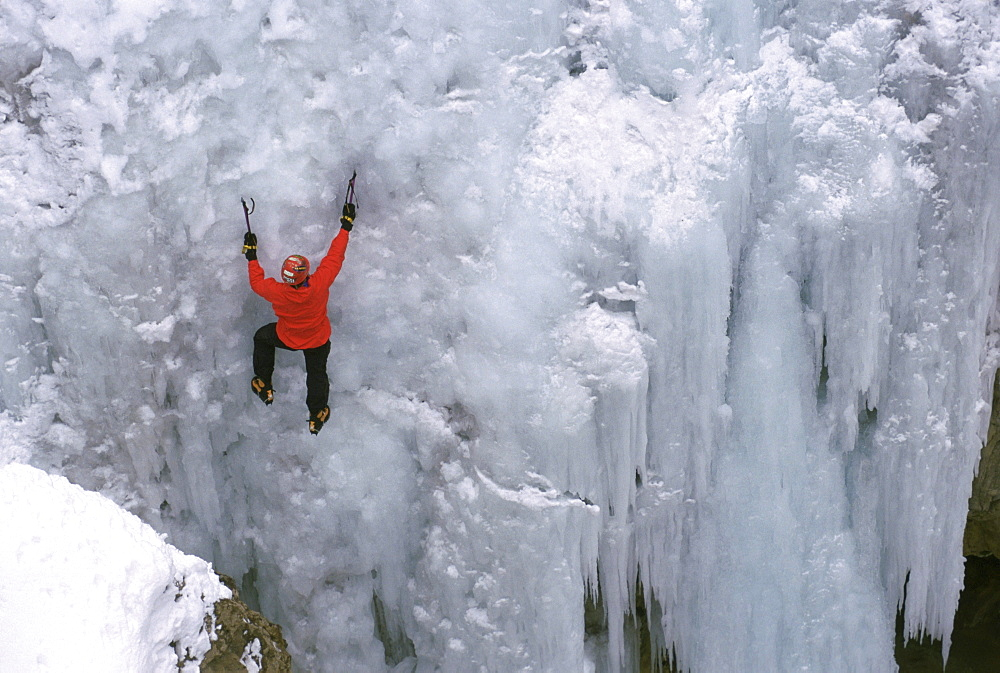 An ice climber ascends a frozen waterfall in Ouray, Colorado.