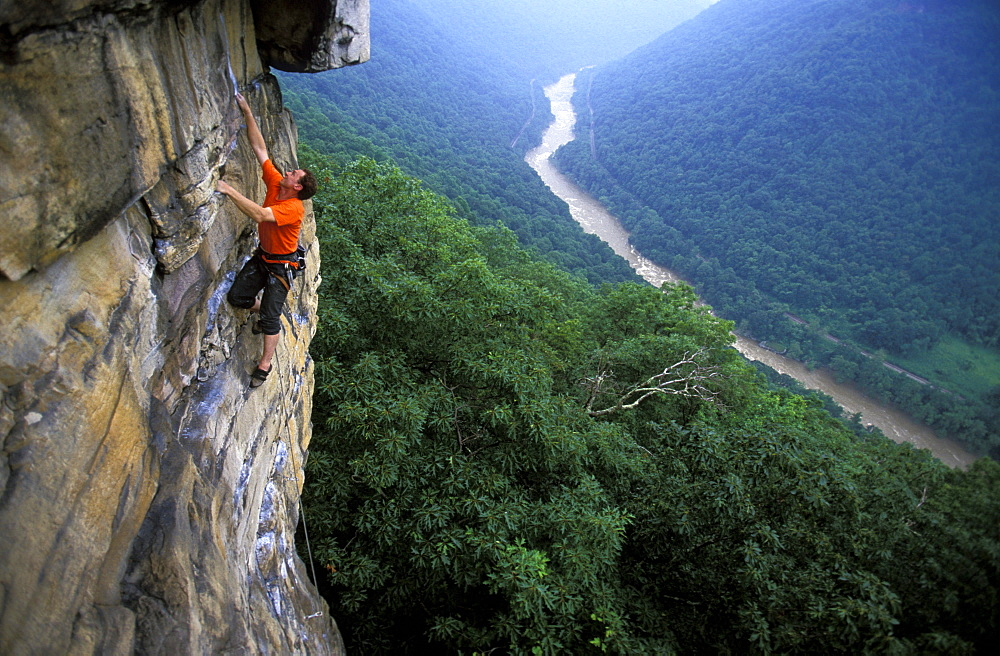 Gene Kissler rock climbing on Discombobulated 5.11a on a sandstone cliff in the New River Gorge, West Virginia.
