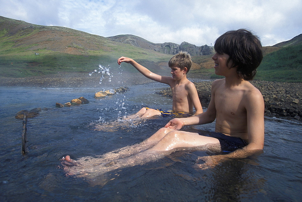 An American boy and an Icelandic boy take a dip in a naturally heated stream in the Valley of Steam near Hveragerdi, Iceland - 857-26968