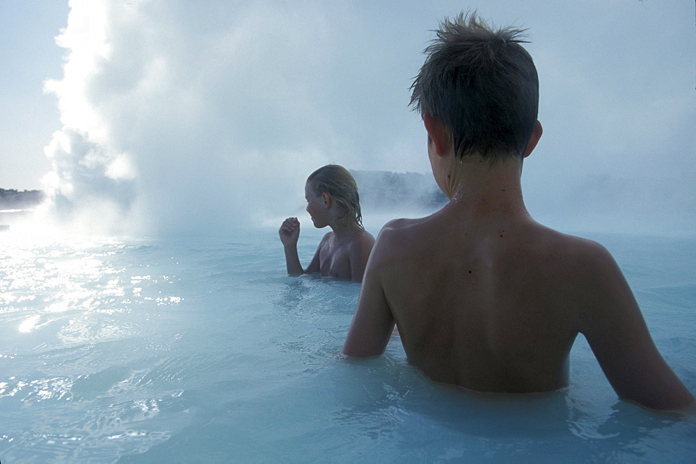 An American boy and an Icelandic boy enjoy the soothing hot water of Blue Lagoon near Reykjavik, Iceland