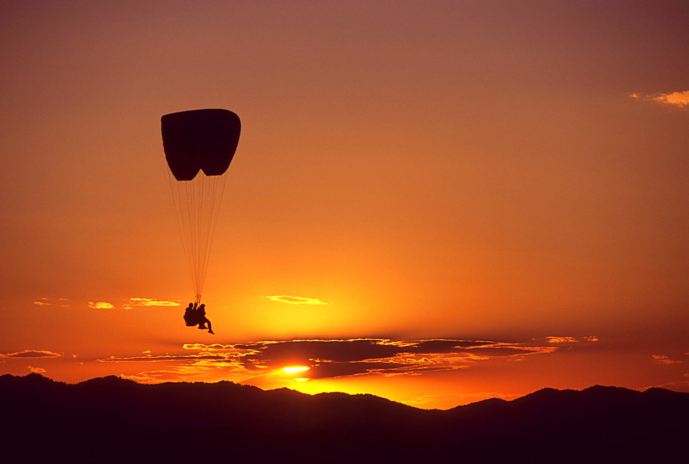 A tandem paraglider pilot and passenger soar over Jackson Hole, Wyoming at sunset.