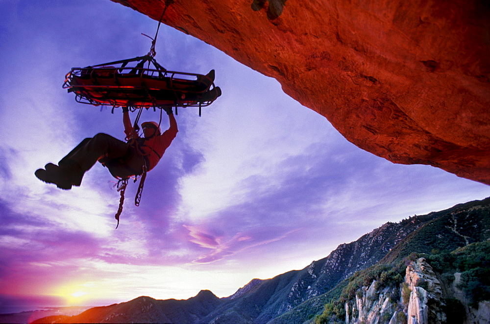 Shannon Black, silhouetted against the sunset sky, tends a Search and Rescue stretcher on the overhanging face of Gibraltar Rock in Santa Barbara, California on January 18, 2003.