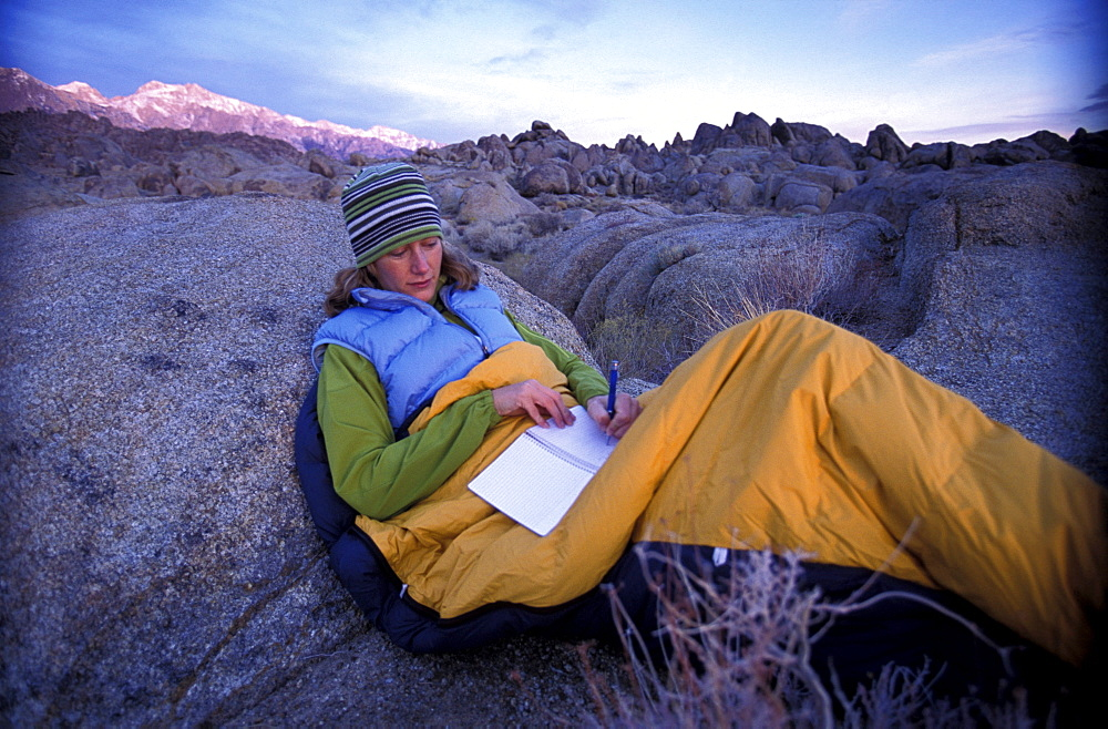 Ashley Laux reads and writes in her notebook while sitting in her sleeping bag to stay warm in the early morning while camping in the Alabama Hills near Lone Pine in the Eastern Sierra Nevada mountains, California.
