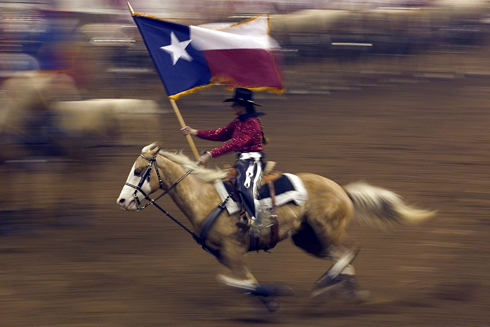 Young cowboy trotting in the arena holding a Texas flag at the San Antonio Rodeo Show.