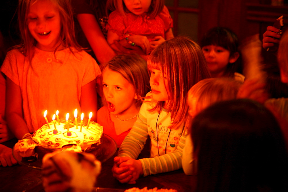 A group of young children gather around a birthday cake and blow candles out.