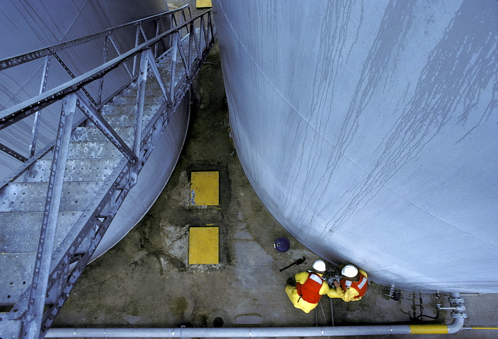 Two men working at the bottom of two cylinder shaped silos are visible from above a ladder at an oil field facility offshore.