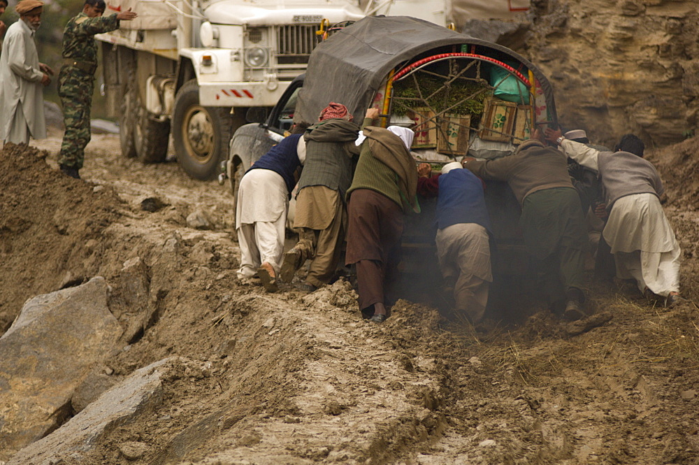 On the the road to the Allai Valley, men try to push a truck  that is stuck in mud and landslide debris and which is blocking other trucks full of humanitarian aid and  earthquake survivors returning to their  mountain villages, Battagram District, Pakistan's Northwest Frontier Province.  The region was one of the worst-hit by the October 2005 earthquake, and aftershocks and  heavy rains continue to trigger landslides, which have hampered reconstruction efforts and the return of earthquake survivors  to their mountain villages from the low altitude tent camps where many spent the winter.