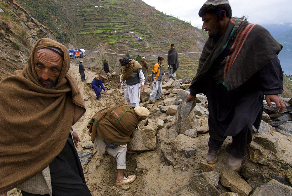 Pashtun men clear rocks from a landslide that is blocking the road to the Allai Valley, and preventing many  trucks    full of  earthquake survivors and their possessions from traveling back to their mountan villages, Battagram District, Pakistan's Northwest Frontier Province.  The region was one of the worst-hit by the October 2005 earthquake, and aftershocks and  heavy rains continue to trigger landslides, which have hampered reconstruction efforts and the return of earthquake survivors  to their mountain villages from the low altitude tent camps where many spent the winter.