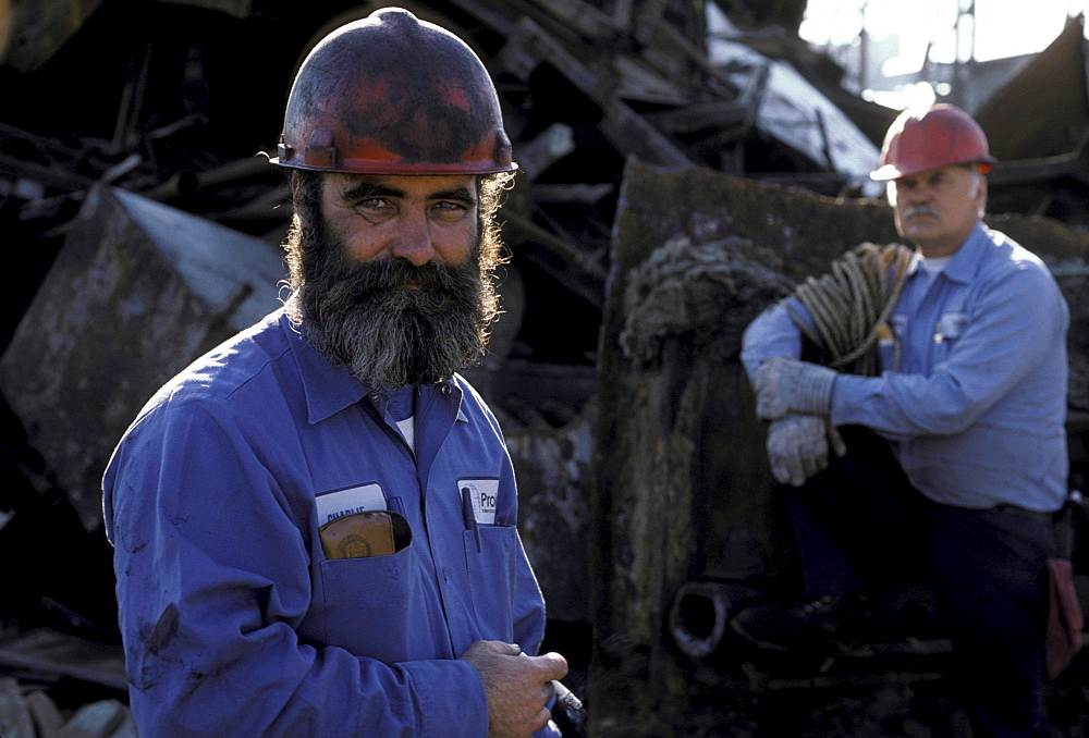 Two oil refinery workers wearing red helmets stands outside for a smoke.