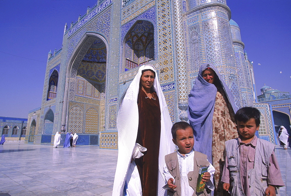 Tajik women proudly pose with their children, burqa's thrown back, in front of the main entrance to the Blue Mosque, Mazar-i-Sharif, Balkh Province.  Wednesday mornings are reserved for women to come and worship at the mosque. Elaborate tilework and decorated spires adorn the mosque, also known as the Shrine of Hazrat Ali (Hazrat Ali was the son-in-law of the prophet Mohammed), who is believed to be buried here.  The shrine, of particular importance for Afghanistan's Shi'ite Muslims, was first built in the 12th century, destroyed by Genghis Khan, and rebuilt in 1481.  The current mosque, considered by some to be one of the most beautiful in Central Asia, is a modern restoration.