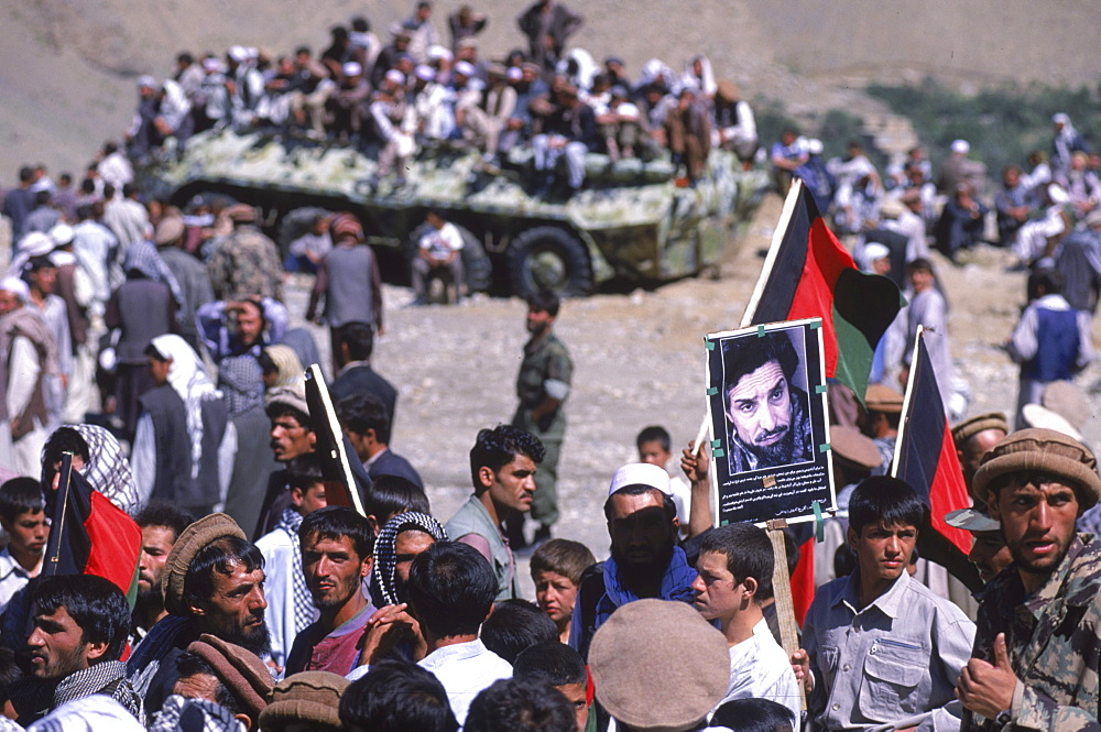Men, soldiers and schoolboys carry banners and photos to the shrine in the Panjshir Valley of the famous Tajik commander, Ahmad Shah Masood, during a memorial on the one year anniversary of his assasination, September 9, 2002.  Masood was a revered mujahedin leader who also was one of the leaders of the Northern Alliance which opposed the Taliban and helped the US Military in their defeat.  Masood was assasinated by what are thought to be Al Queda operatives on Sept. 9, 2001.  A shrine has been erected in the Panjshir  Valley  from where he led much of his resistance to both the Soviet and Taliban forces, to honor this latest of Afghan war heros.