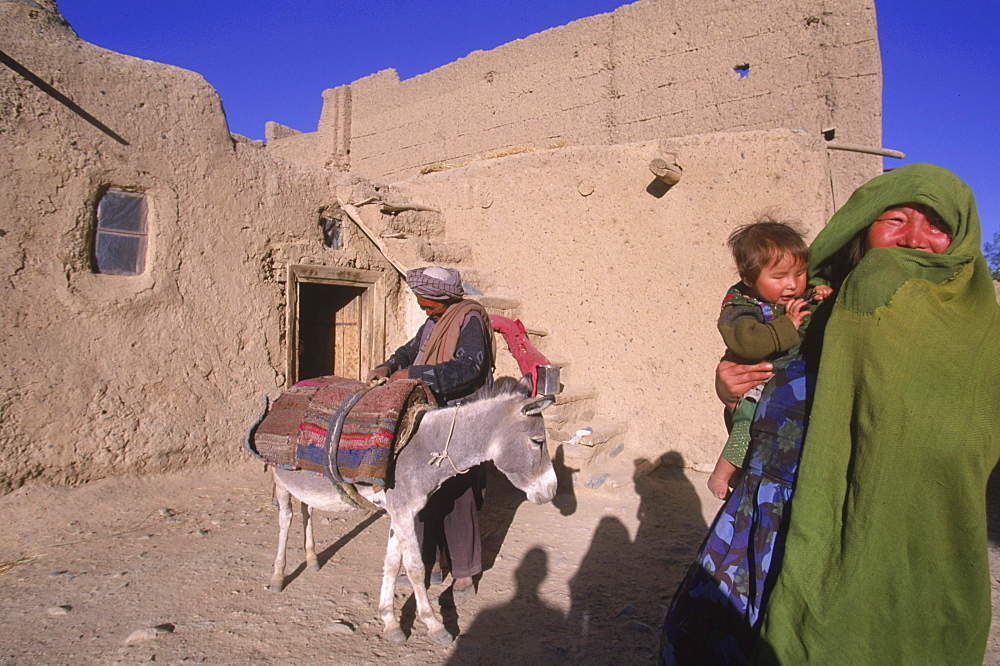 Striking Mongol features distinguish the face of a woman and her child (who is blind) living in the ruins of the Qala-i-Dokthar (Daughter's Castle), outside of the town of  Bamiyan, August 30, 2002.  Most of the old town was destroyed and up to 20,000 people of the region might have perished when Bamiyan fell to the Taliban in 2001.   Bamiyan Valley is located in the Hazarajat at the edge of the Koh-i-Baba range , the end of the Hindu Kush.  Bamiyan was a prosperous Buddhist kingdom on the ancient Silk Road until the 10th century, when the region  was converted to Islam; in the 12th century, it was destroyed by Ghengis Khan. Most of the people of this region are of the Hazara tribe, and are Shi'a Moslems who have been persecuted for centuries by many of the Pashtun rulers of Afghanistan, who are from the Sunni sect.  They most recently suffered at the hand of the Taliban, who tried for years to ethnically cleanse the region of its Shi'a people.