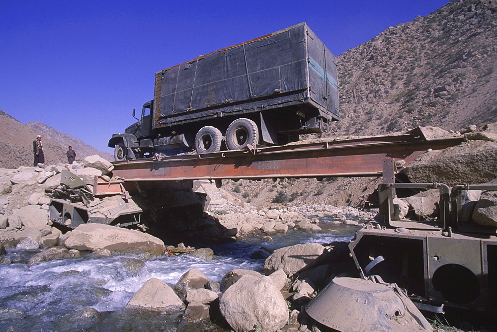 A truck  drives over a makeshift bridge supported by ruined tanks on the road north of the Salang Tunnel in Baghlan province, August 31, 2002.  High  in the mountains of the Hindu Kush, the road was destroyed several years ago by a flood from raging mountain rivers.  The road was improved  by the Soviets after their 1979 invasion of Afghanistan, and was a crucial link for troops and supplies coming from the Soviet Union.  The mountain road is in terrible condition, and its repair is crucially important for the reconstruction of the country