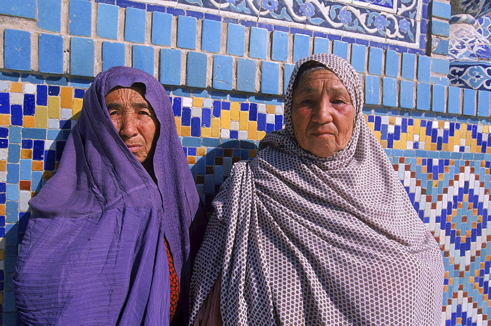 Uzbek women peek out from their veils in front of the tiled wall of the Blue Mosque, Mazar-i-Sharif, Balkh Province. The Blue Mosque is considered to be one of the most important and beautiful buildings in Afghanistan.  The region around Mazar-i-Sharif is the center of the Uzbek tribe in Northern Afghanistan