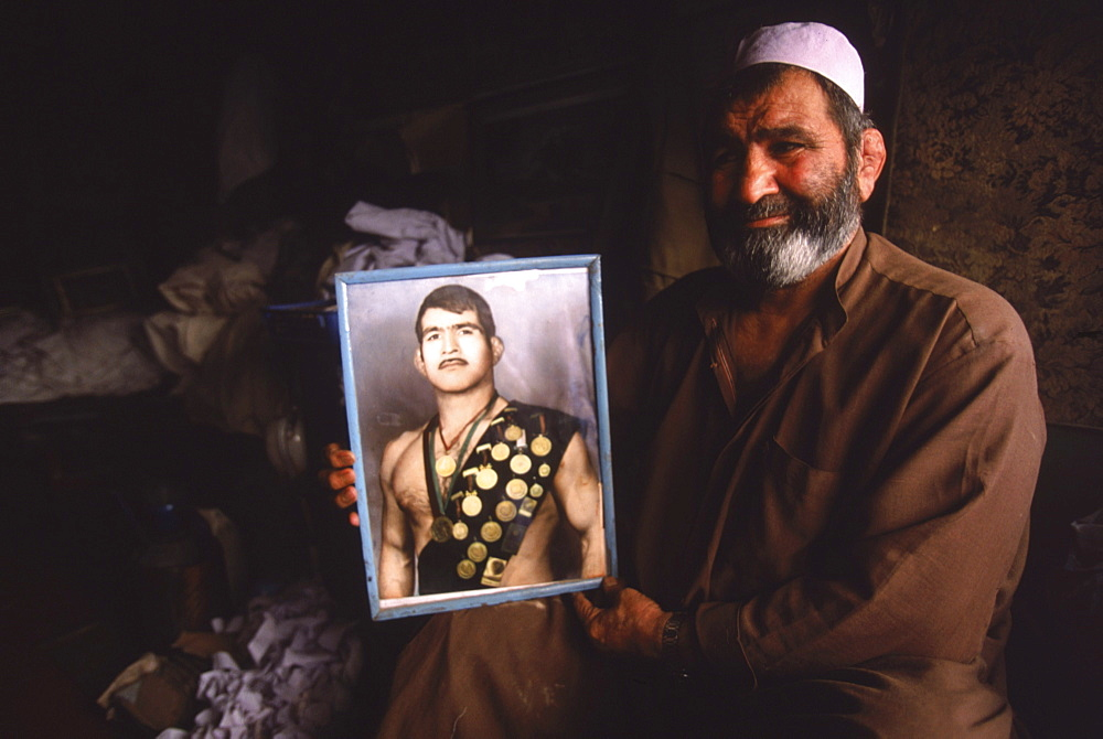 An Afghan man holds a portait of himself as an Olympic wrestler in one of the old bazaars of Kabul.  The man, now working as a traditional healer in a tiny stall, had been part of the Afghan Olympic team in the 1970's and had competed in Europe and in Mexico City.