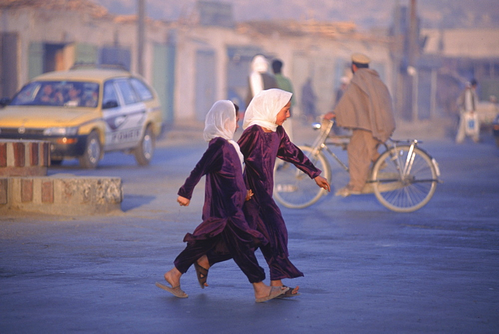 Two school girls hurry across a street at dawn in Kabul, Afghanistan.  Since the fall of the Taliban, a record number of girls have returned to school throughout Afghanistan. Much of Kabul  was  destroyed in the mid 1990's (1992-1996) in factional fighting between rival mujahideen commanders for control of the capital after the Soviet's withdrawal, and now Afghans are re-building their lives and business