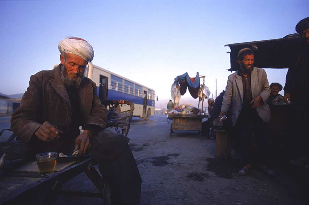 An Afghan man sits on his wooden cart and drinks tea at dawn from a street tea stall in central Kabul.    With the first  respite from war in nearly two decades, Kabulis are busy re-building their lives and business amongst the ruins, and the streets are busy with markets, tea stalls, trucks, etc.  Much of Kabul  was  destroyed in the mid 1990's (1992-1996) in factional fighting between rival mujahideen commanders for control of the capital after the Soviet's withdrawal.
