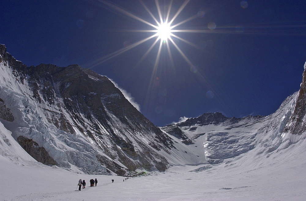 Climbers make their way to Advanced Basecamp (ABC) through the massive Western Cwm (glacial valley) on the Southeast Ridge route on Mt. Everest, Nepal. Everest's Southwest Face rises to the left with Lhotse and the Lhotse Face in the distance. Jake Norton, 4, 20, 2002, Western Cwm, Everest, Nepal. - 857-34122