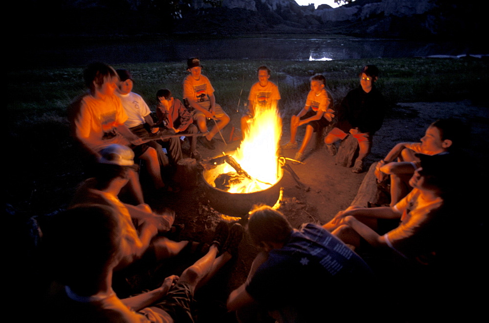 Boy Scout troop  sits around a campfire while camping on the Upper Missouri River in Montana.