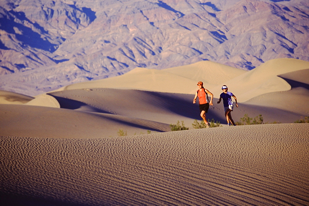 Two women running on a sand dune in Death Valley, California.