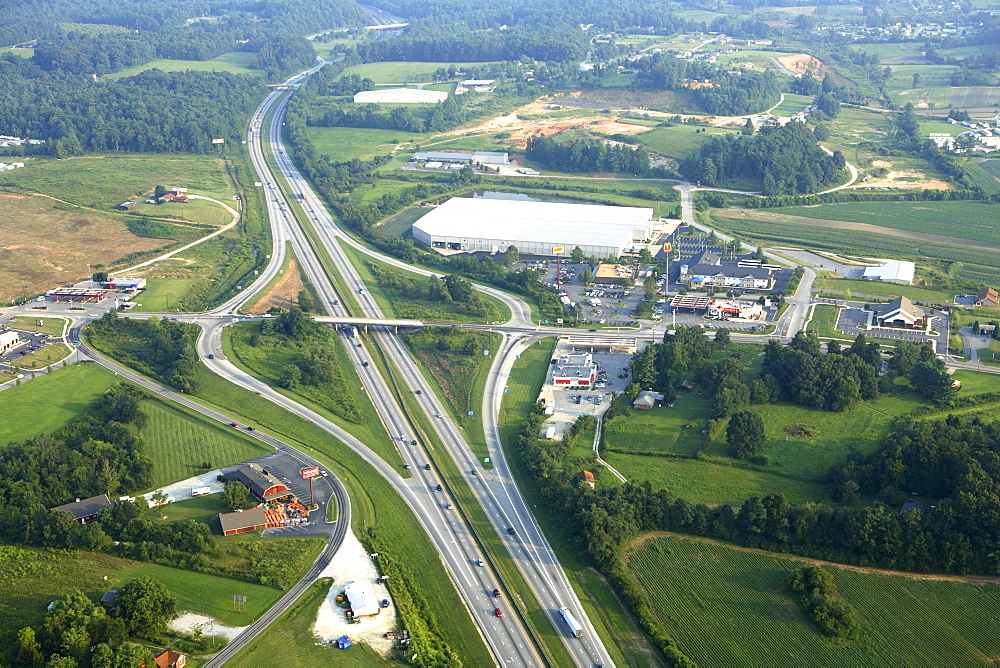 Aerial view of commercial growth clustered around an interstate exit near Hendersonville, NC.