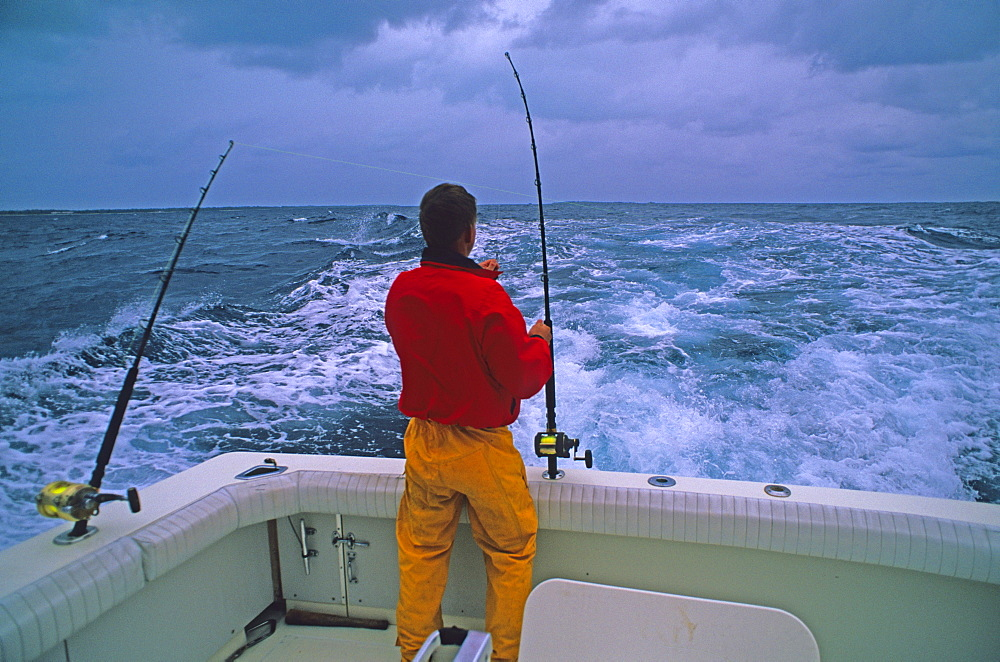 A fisherman rigs trolling lines for big game fish in the Pacific Ocean off Midway Atoll, Hawaii.