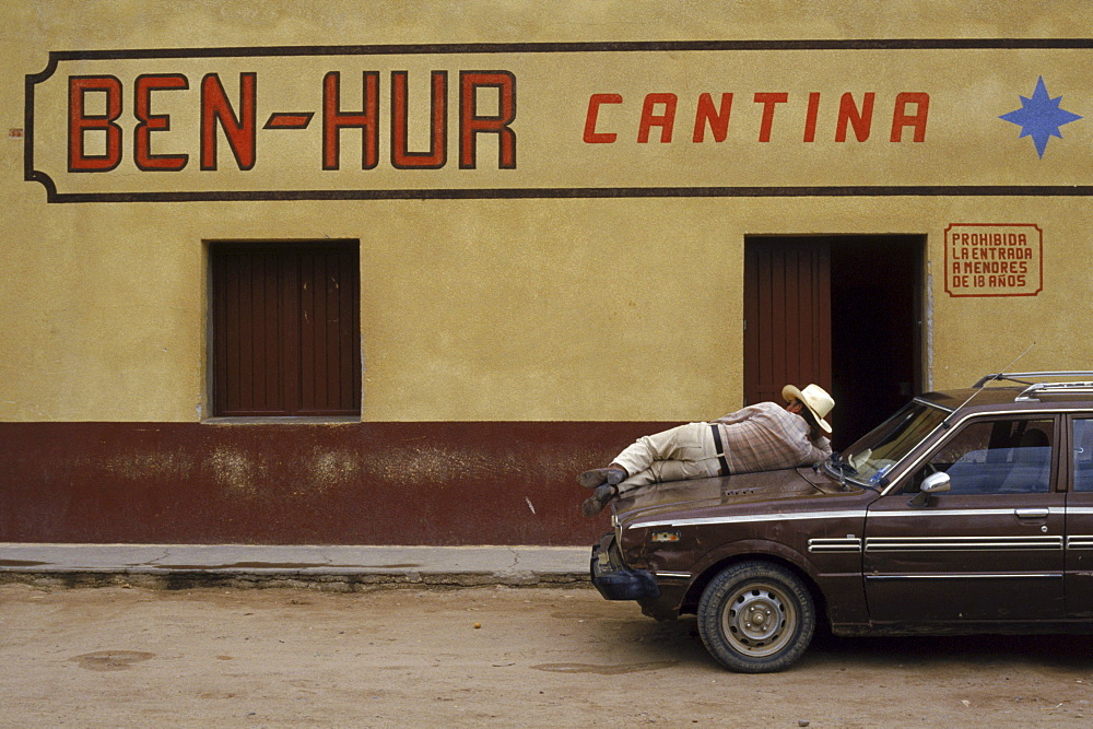 A patron of the Ben-Hur cantina relaxes on the hood of his car on a quiet afternoon in Trincheras, Mexico.