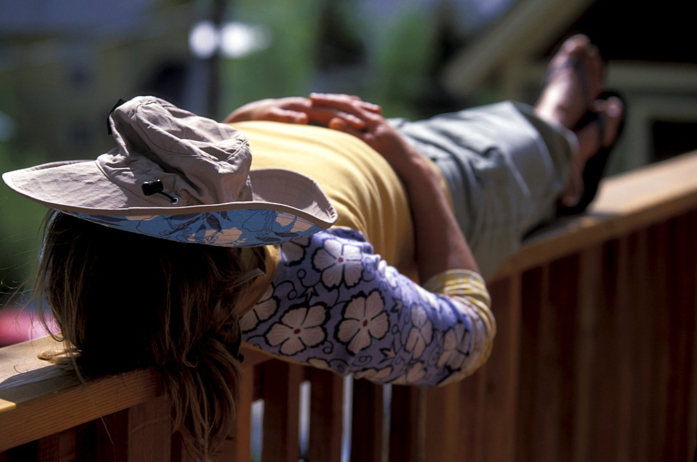 A woman napping on a railing with a hat over her face in Telluride, Colorado.