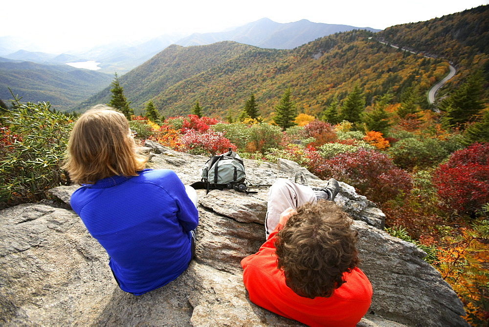 Young couple soaks in the view of the fall colors and the Blue Ridge Parkway from Potato Knob while hiking the Mountains-to-Sea