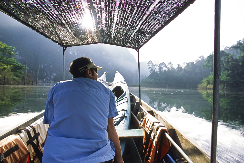 A young man rides a longtail boat shuttle across Chiaw Lan Lake in Khao Sok National Park, Thailand.