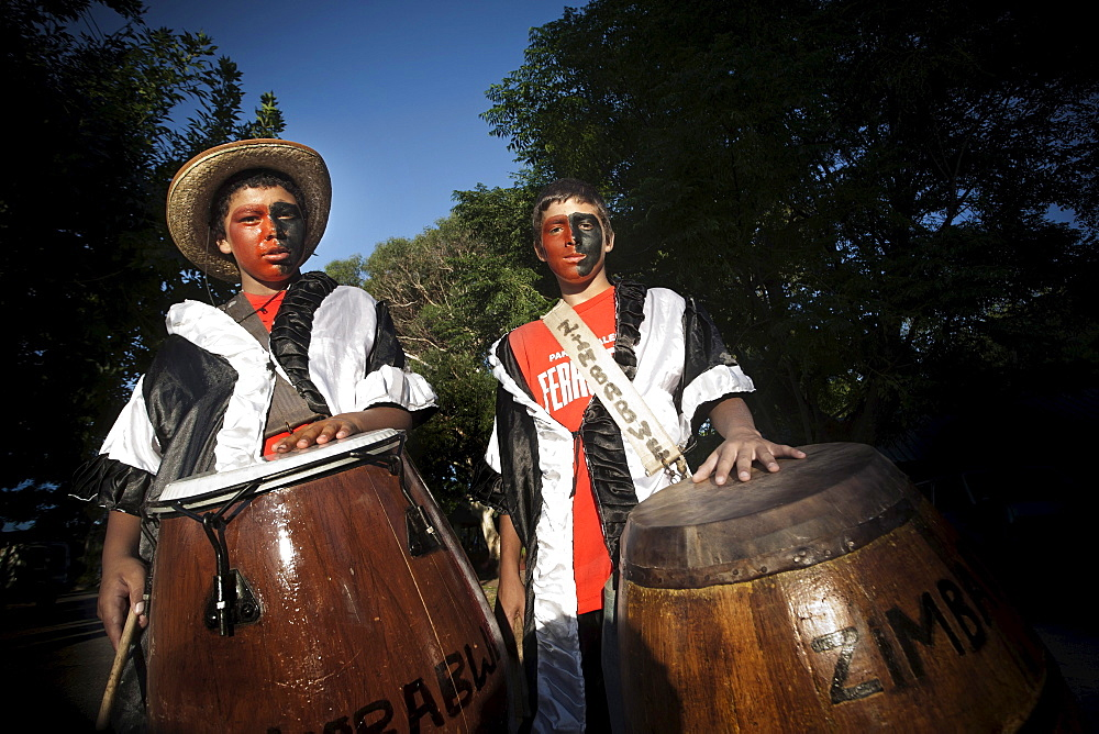 """Two kids with their faces painted carrying drums to play at the """"llamadas"""" during the Carnaval in Colonia del Sacramento, Uruguay."""