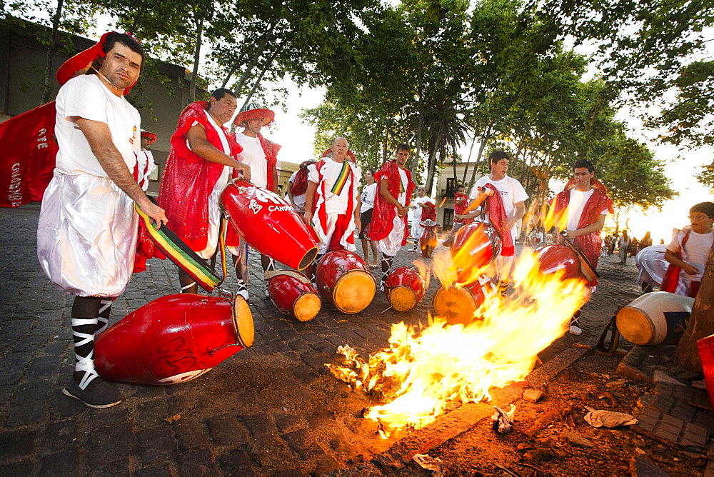 """A group of men heating the drums before playing at the """"desfile de llamadas"""" during the carnival celebrations in Colonia del Sacramento, Uruguay."""