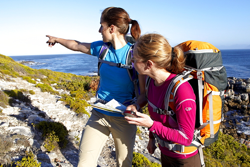 Katrin Schneider and Susann Scheller checking a handheld GPS device while hiking on an ocean trail between Gansbaai and De Kelders. South Africa.