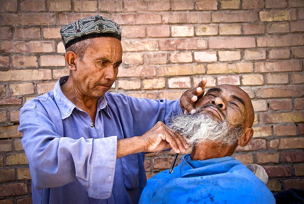 Street barber, Kashgar, Xinjiang Province, China.