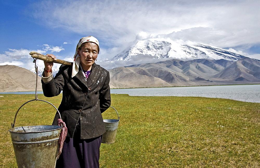 Local woman carrying water, Karakul lake, Karakoram Highway, Xinjiang Province, China