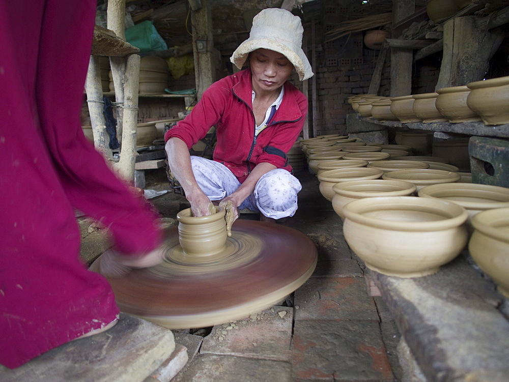 Workers making ceramics with foot powered wheel in Hoi An, Vietnam