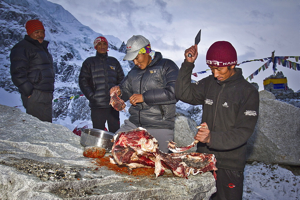 Two cooks for Jagged Globe Everest Expedition prepares Yak meat at Everest Base Camp while two sherpas watch