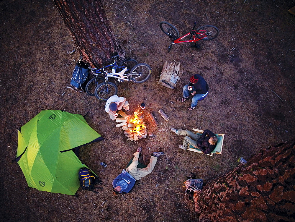 Friends gather outside their tent around the camp fire at a picnic on the beach.