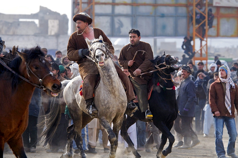 Afghan men on horseback turn their horses toward the action during a game of