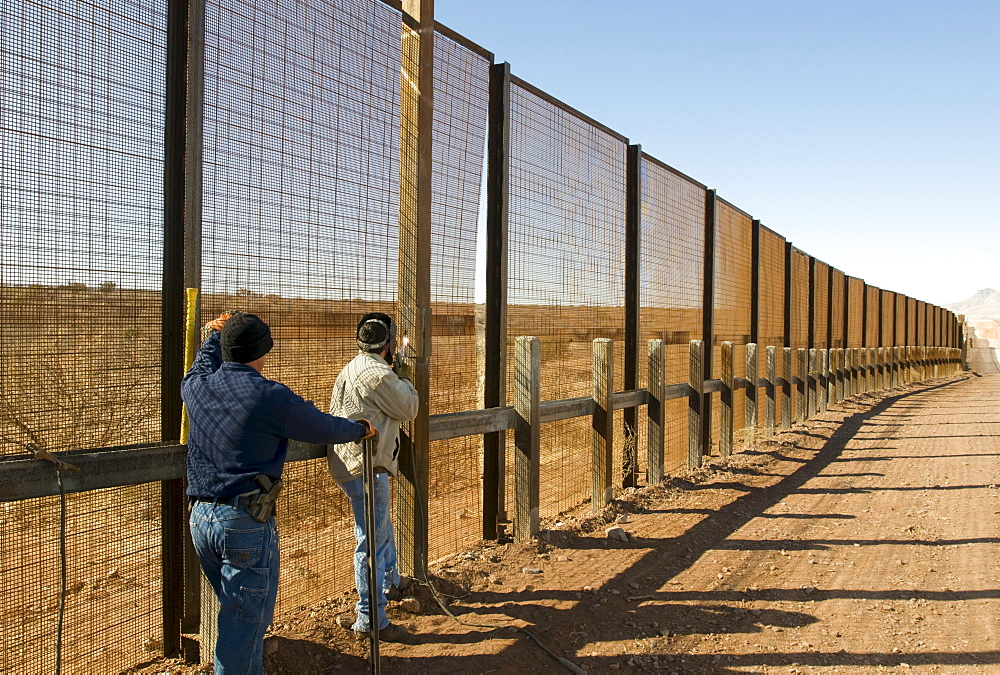 Welders repair the pedestrian border fence with Mexico, AZ.