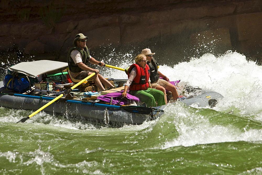 A river guide navigates his boat through rapids.