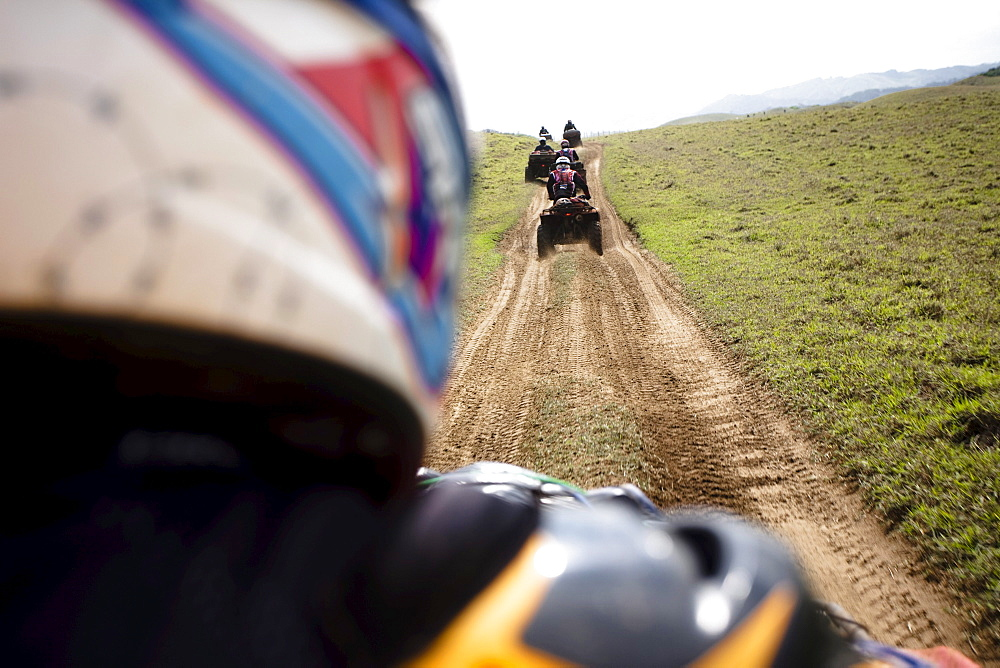 A group of man rides their quads through a dirt road from Catemaco to Coatzacoalcos in Veracruz, Mexico.