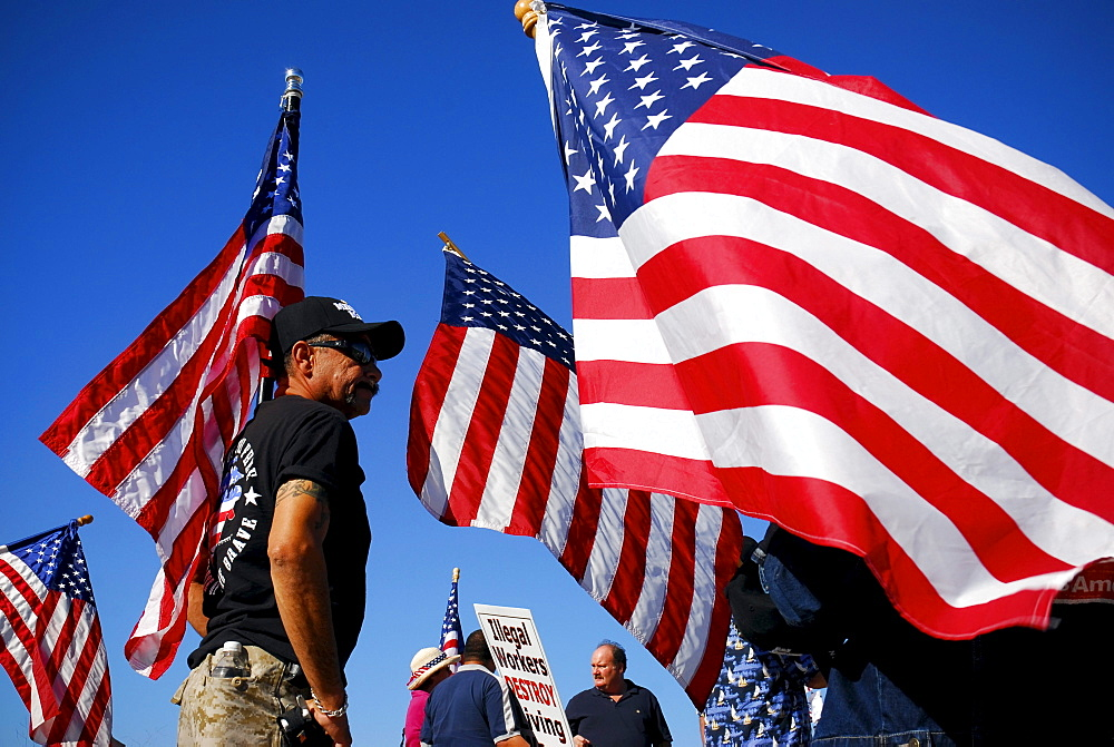 An immigration activist stands surrounded by waving American flags at a Minute Men ralley in San Diego, California.